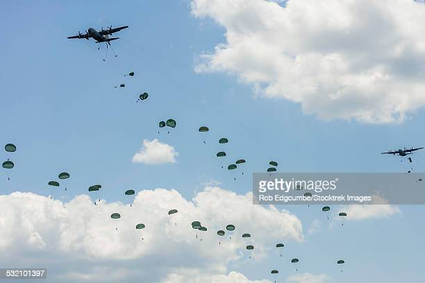 u.s. air force c-130 hercules drop u.s. army airborne troops over andrews air force base, maryland. - paratrooper stock pictures, royalty-free photos & images
