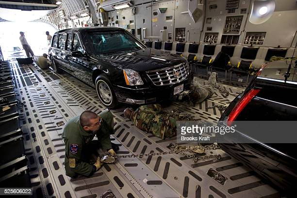 Air Force crew secure two Presidential limousines inside a C5 military transport plane bound for eastern Europe where President Bush is headed next...