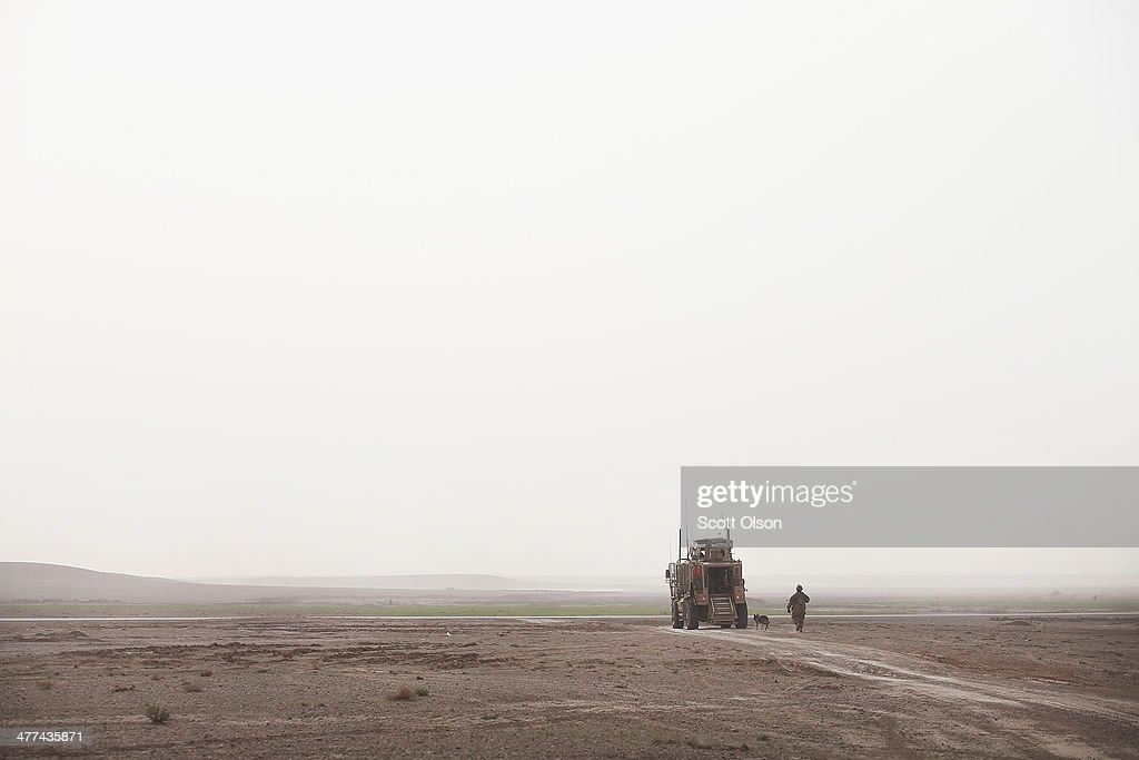S. Air Force dog handler returns to his vehicle after a patrol with soldiers from the U.S. Army's 4th squadron 2d Cavalry Regiment on March 9, 2014 near Kandahar, Afghanistan. President Obama recently ordered the Pentagon to begin contingency planning for a pullout from Afghanistan by the end of 2014 if Afghanistan President Hamid Karzai or his successor refuses to sign the Bilateral Security Agreement.