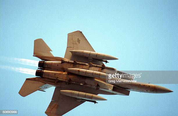 Air Force F15 armed with missiles and long range fuel pods flying overhead on its way to targets in Iraq during Operation Desert Storm