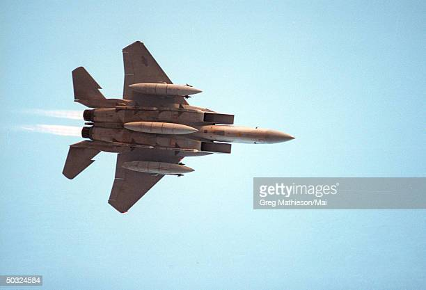 US Air Force F15 loaded and armed with missiles bombs and long range fuel pods flying overhead on its way to targets in Iraq during Operation Desert...