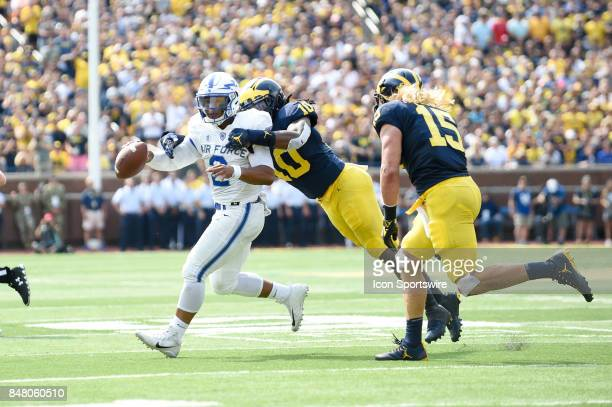 Air Force Falcons quarterback Arion Worthman runs wide trying to pass as he's tackled for a loss by Michigan Wolverines linebacker Devin Bush during...