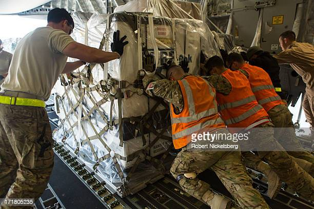 Air Force flight line crew push a pallet of material off a C-17 cargo plane May 11, 2013 at Bagram Air Base, Afghanistan.