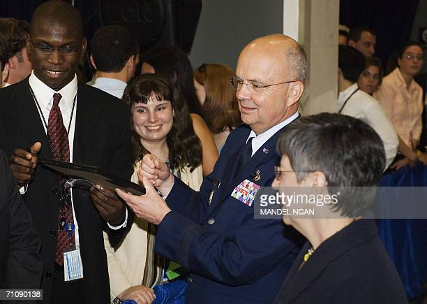 Air Force General Michael Hayden signs an autograph as his wife Jeanine watches after his ceremonial swearingin as the new director of the Central...