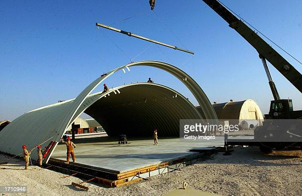 Air Force members from the 819th/219th Expeditionary Rapid Engineering Deployable Heavy Operation Repair Squadron Engineers guide a Kspan arch...