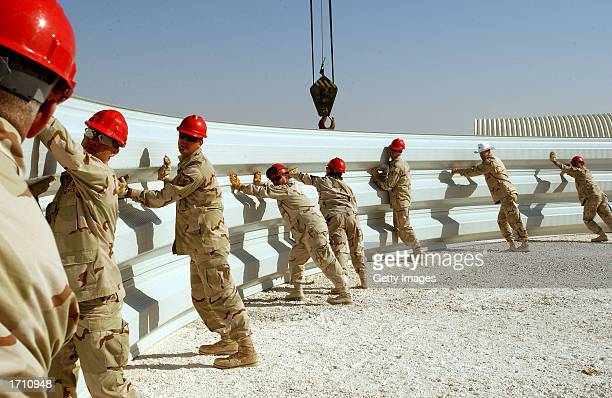 Air Force members from the 819th/219th Expeditionary Rapid Engineering Deployable Heavy Operation Repair Squadron Engineers put building arches...