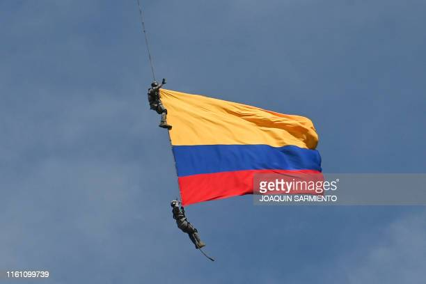 TOPSHOT Air Force members Jesus Mosquera and Sebastian Gamboa hang from an helicopter as they wave a Colombian flag as part of a performance during...