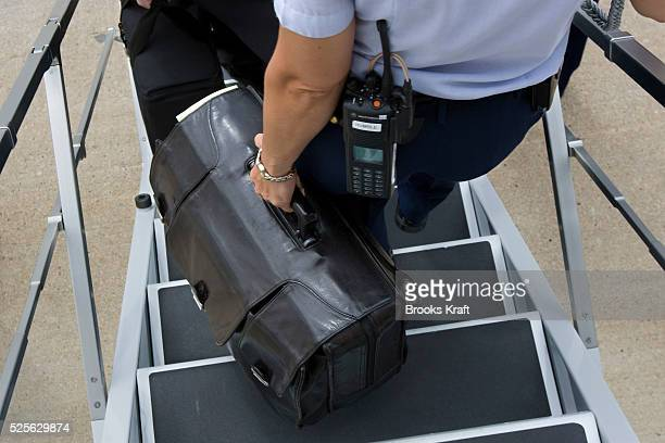 A US Air Force military aide carry 'The Football' off Air Force One in Raleigh NC The Football is a specially outfitted black briefcase used by the...