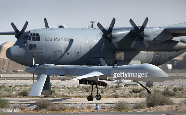 S Air Force MQ1B Predator unmanned aerial vehicle carrying a Hellfire airtosurface missile passes a C130 Hercules cargo plane at a secret air base in...