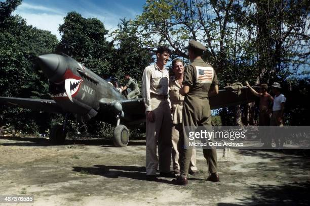 S Air Force Officer of The 51st Fighter Group talks with maintenance workers as a P40 Warhawk in the background at the US Airfield base in DinjanIndia