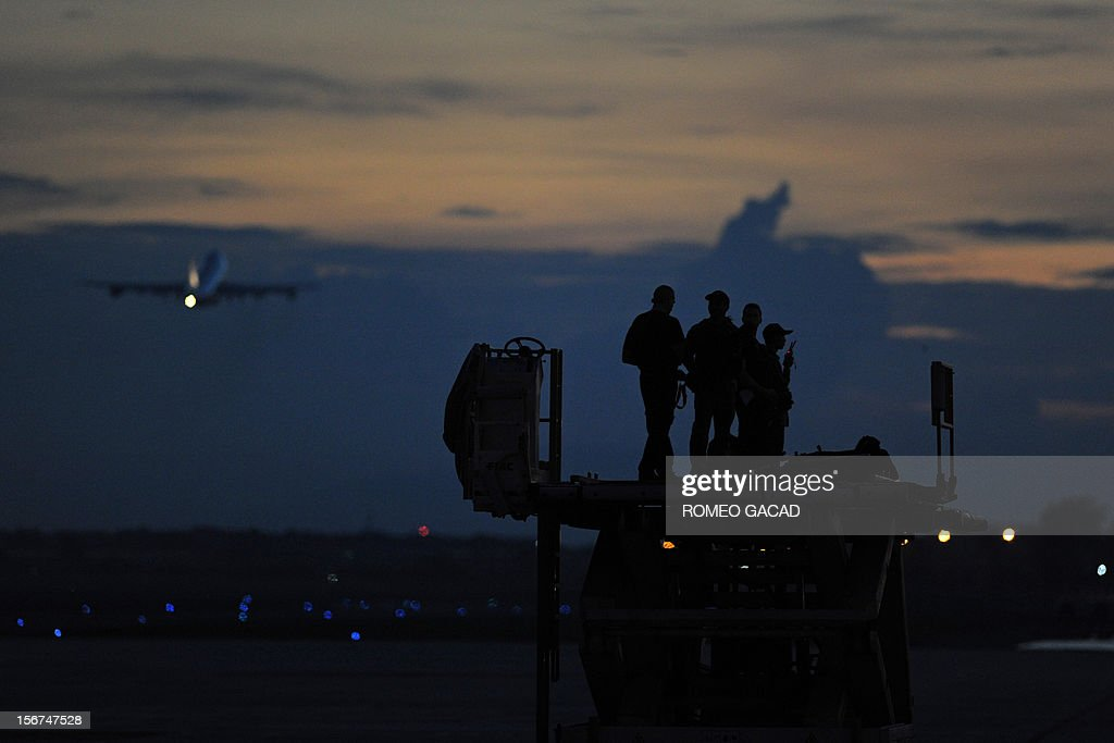 Air Force One (L, background), carrying US President Barack Obama, takes off from Phnom Penh airport as US security personnel keep watch on November 20, 2012. US President Barack Obama on Tuesday defied Chinese protests and raised concerns at a summit about territorial disputes that have sent diplomatic and trade shockwaves across the region.