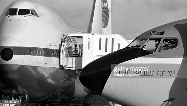 Air Force One with 'The Spirit of '76' painted on its nose taxis into position in front of a Pan American Airlines Jumbo Jet on the tarmac at Agana...