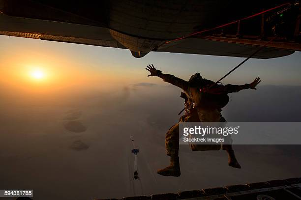 a u.s. air force pararescueman jumps from an hc-130p/n combat king. - night before stock photos and pictures