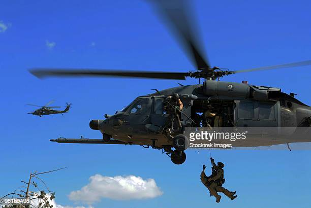 u.s. air force pararescuemen are hoisted into an hh-60 pavehawk helicopter. - helicopter rotors stock photos and pictures