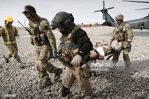 Air Force Pedro Med Evac personnel carry a stretcher with a wounded British soldier from their helicopter into an ambulance in Camp Bastion on...