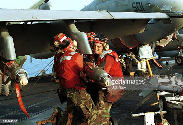 Air Force Personnel Move Ordnance Into Place October 7, 2001 While On Board The USS Enterprise. Aircraft Are Readied For Strike Missions Against Al...