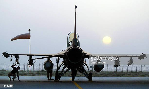 S Air Force pilot performs a basic post flight inspection on an F16 Fighting Falcon at an airbase near sunset as American forces get ready for a...