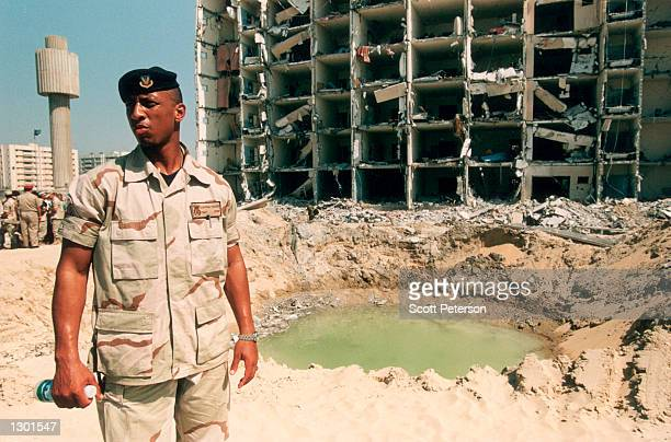 A US Air Force sargeant stands in front of a bomb crater during a tour of the wreckage of Khobar Towers in Dhahran Saudi Arabia June 29 1996 after a...