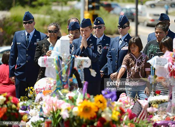 Air Force Senior Master Sgt Raea Thompson from nearby Buckley Air Force base prays as she and her fellow servicemen visit theater shooting victim...