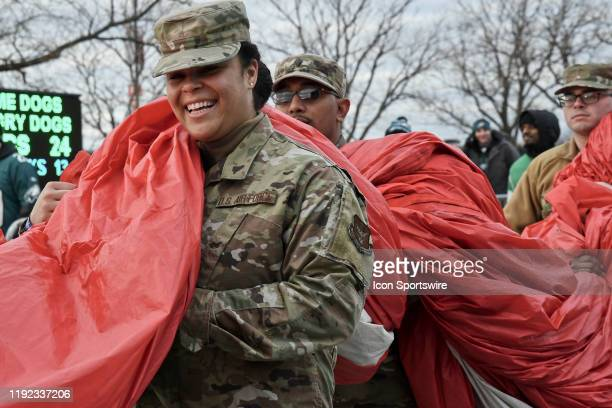 Air Force service member helps carry the flag during the Playoff game between the Seattle Seahawks and the Philadelphia Eagles on January 5 at...