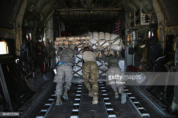 S Air Force service members push cargo onto a Texas Air National Guard C130 cargo plane bound for Iraq on January 10 2016 from a base in an...
