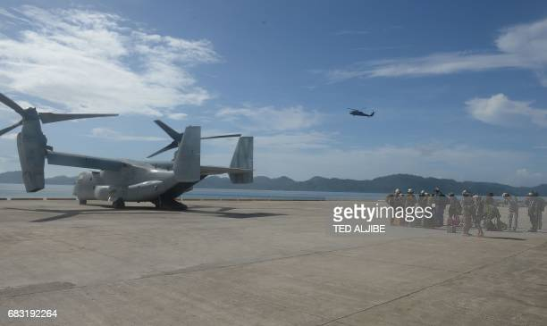 A US air force V22 Osprey aircraft sits after unloading US marines while a US army black hawk helicopter hovers above during a simulation of a...