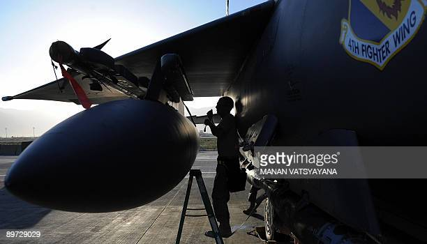 Air Force weapons management crew inspects a bomb on an F-15E Strike Eagle fighter jet at the Bagram AirBase, in the Parwan province some 50kms north...