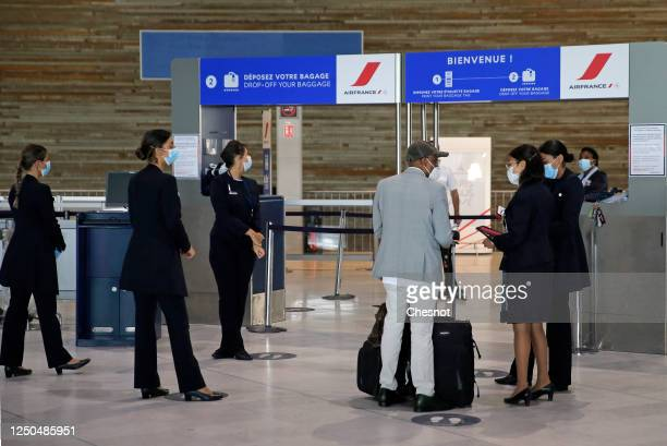 Air France employees wearing protective face masks check a passenger at Paris Charles de Gaulle airport on June 18, 2020 in Roissy-en-France, France....