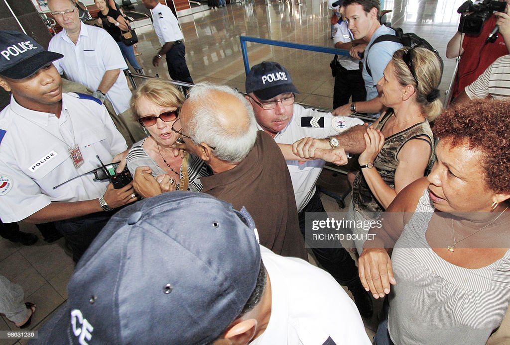 Air France passengers face policemen at Gillot airport in the French Indian ocean island of Saint Denis de la Reunion on April 22, 2010. Two thousand and five hundred passengers are stuck after Air France national company didn't charter enough planes as traffic air returned to normal. Nearly seven million passengers have been affected in the world by the disruption of air traffic due to the volcano eruption in Iceland.