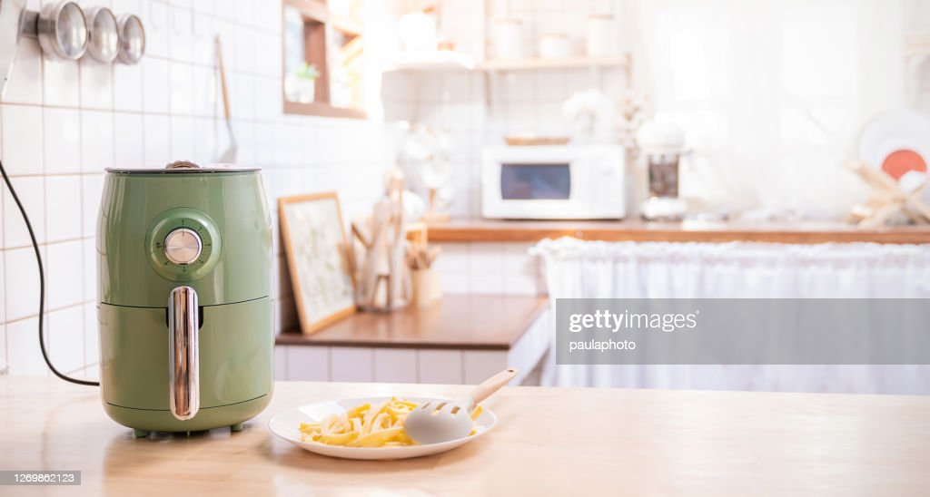 Air fryer machine cooking potato fried in kitchen home. New normal cooking at home lifestyle. Technology eco friendly home smart device. Air fryer machine with french fried concept : Stock Photo