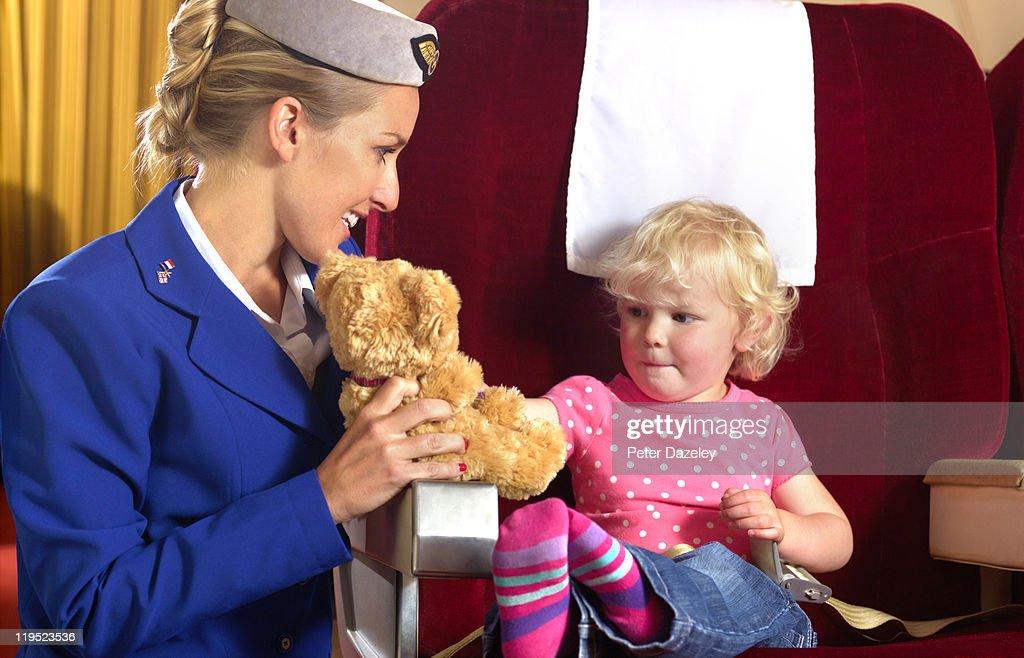 Air hostess entertaining child on airplane : Stock Photo