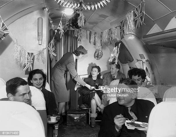 Air hostess Patricia Pelley serves an inflight meal to passengers traveling across the Atlantic on board a festively decorated PanAmerican aeroplane