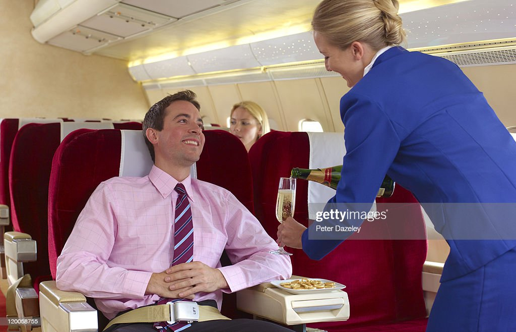 Air hostess pouring champagne in first class : Stock Photo
