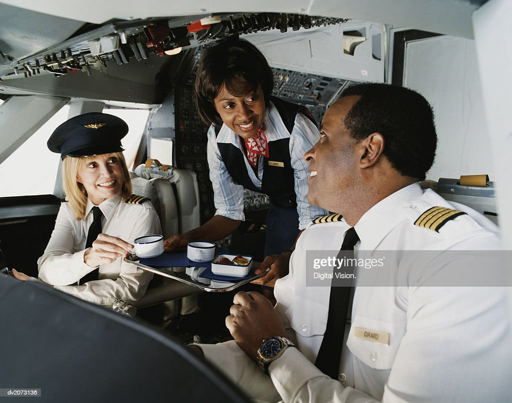 Air Hostess Serves Coffee to the Pilots in the Cockpit : Stock Photo