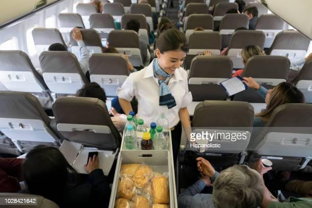 aeromoça, servindo comida e bebidas a bordo - tripulação de bordo - fotografias e filmes do acervo