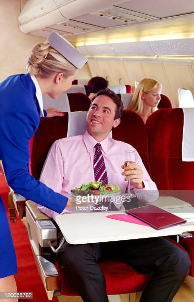 Air hostess serving food in first class