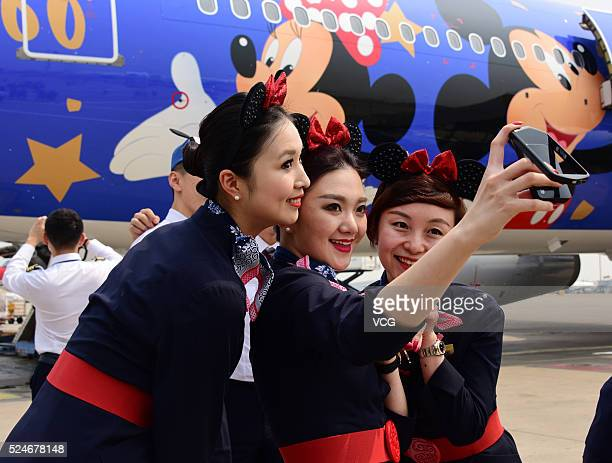 Air hostesses wearing Minnieear hair clips take selfies with the Disneythemed plane after its debut from Shanghai to Beijing on April 26 2016 in...
