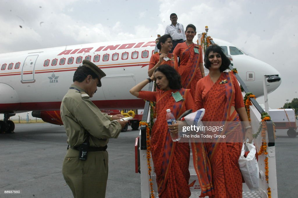 Air India air hostesses, wear their new uniform atop the Air India flight, during the delivery of the Boeing 737-800 VT-AXH to its own fleet at Indira Gandhi International Airport in New Delhi, India ( Air India-Express, Aeroplane, Indian Airline, Inaugur : News Photo