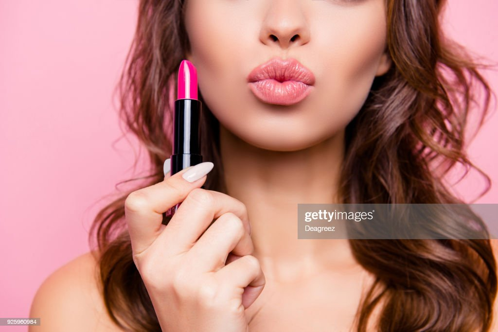 Air kiss for you. Close up cropped shot of femenine gorgeous charming adorable lady with amazing wavy hair do, tube of hard pink pomade in arm. Pampering, lips correction concept : Stock Photo