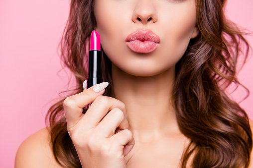 Air kiss for you. Close up cropped shot of femenine gorgeous charming adorable lady with amazing wavy hair do, tube of hard pink pomade in arm. Pampering, lips correction concept 925960984