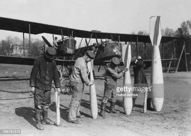 Air mechanics with a selection of armaments carried by the Gotha GV long range heavy bomber of the Luftstreitkrafte on 1 March 1918 at an airfield in...