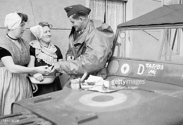 Air Ministry Second World War Official Collection, An R.A.F. Sergeant shares an alfresco lunch with two Dutch women at Nieuland, near Middelburg,...