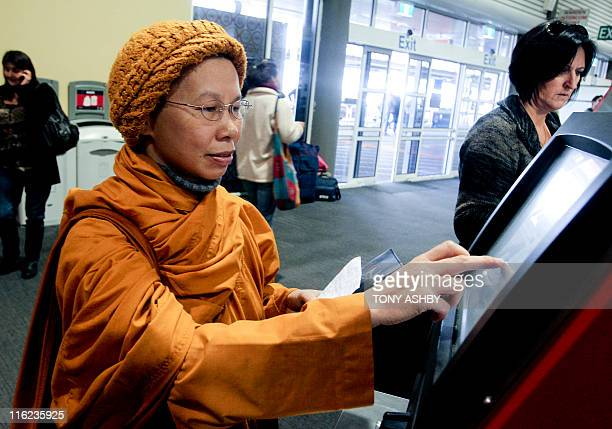 Air passenger Minh Hoa a nun from Hanoi attempts to check in at the Virgin Australia automatic machine as flights are suspended owing to the Chilean...