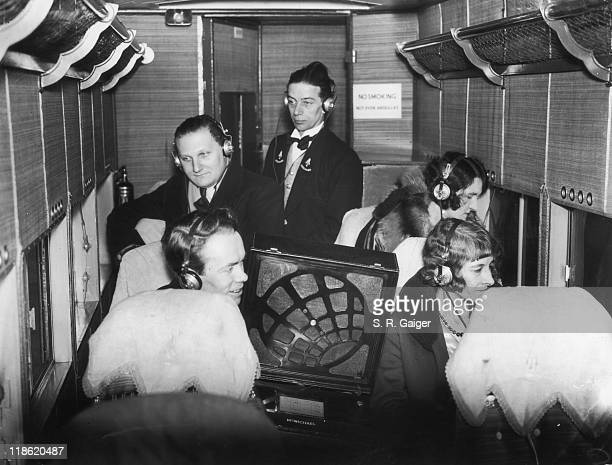 Air passengers and crew wearing headphones experience the first broadcast on an airliner during a test in Croydon London England United Kingdom 9...
