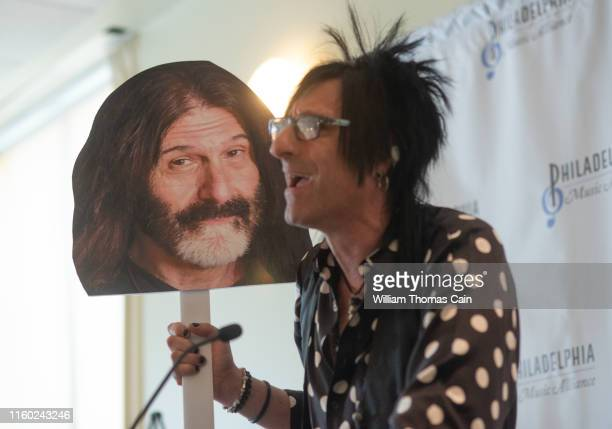 WMMR air personality Jacky Bam Bam holds an oversized picture of WMMR air personality Pierre Robert as he speaks on Robert's behalf after he was...