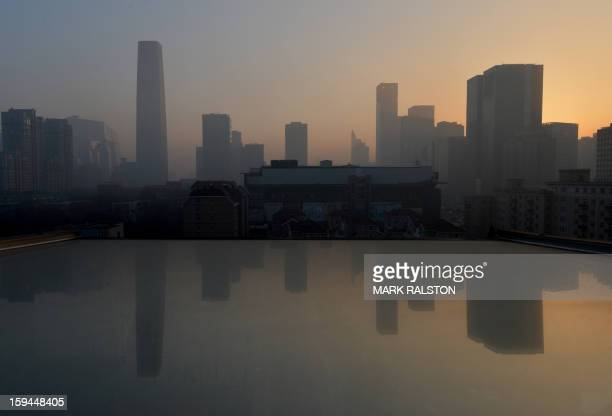Air pollution hangs over the skyline as the sun rises over the central business district in Beijing on January 14 2013 Dense smog shrouded the city...