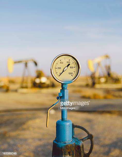 air pressure gauge, oil rigs in background, sunset-midway oil fields, the largest in california. - pressure gauge stock photos and pictures