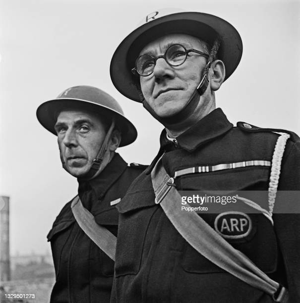 Air Raid rescue squad wardens Thomas Joseph Grant and Thomas Tolen stand together on a bomb site in Liverpool, England during World War II on 19th...