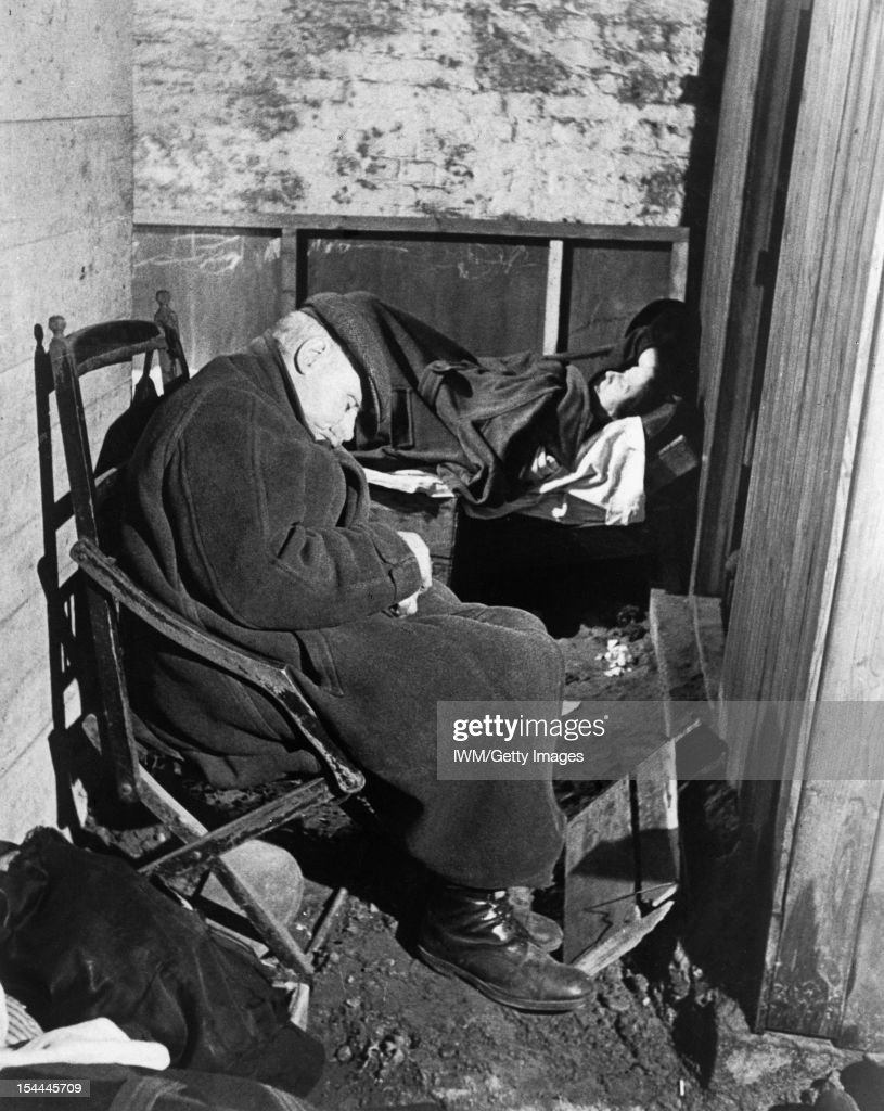 Air Raid Shelter Under The Railway Arches, South East London, England, 1940, An elderly man sleeps on an old wooden chair, whilst a lady covered with a blanket lies on a bed of boxes, under the railway arches somewhere in South East London, probably in November 1940, November 1940.