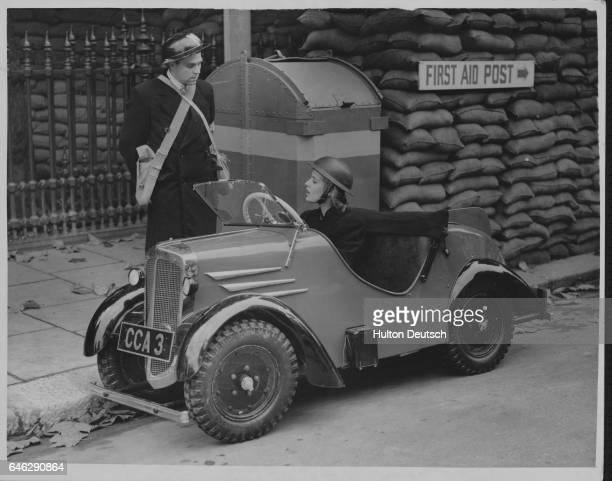 Air Raid Warden driving a miniature car capable of covering eighty miles on a gallon of gasoline and attaining a speed of 45 mph developed to save on...